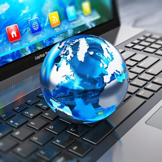39929643 - creative abstract global computer communication and internet business telecommunication concept: macro view of crystal earth globe on laptop or notebook keyboard with selective focus effect